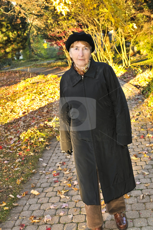 Senior woman in fall park stock photo, Senior woman walking alone in fall park by Elena Elisseeva