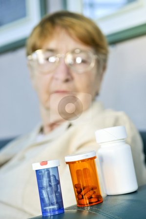 Elderly woman with pill bottles stock photo, Elderly woman sitting and looking at pill bottles by Elena Elisseeva
