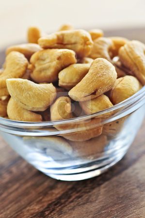Cashew nuts in glass bowl stock photo, Close up of cashew nuts in glass bowl by Elena Elisseeva