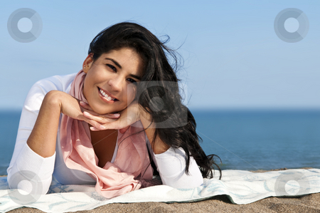 Young native american woman at beach stock photo, Portrait of beautiful smiling native american girl laying at beach by Elena Elisseeva