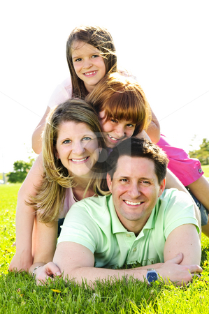 Happy family stock photo, Portrait of happy family of four laying on grass at the park by Elena Elisseeva