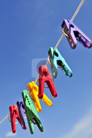 Colorful clothes pins stock photo, Colorful clothes pegs on line against blue sky by Elena Elisseeva