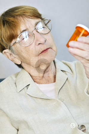 Elderly woman with pill bottle stock photo, Elderly woman reading pill bottle label with glasses by Elena Elisseeva