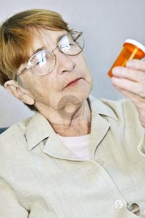 Elderly woman with pill bottle stock photo, Elderly woman reading pill bottle label with glasses by Elena Elisseeva