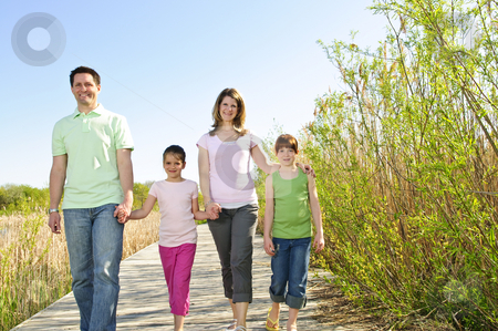 Happy family stock photo, Portrait of happy family of four walking on boardwalk by Elena Elisseeva