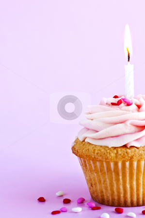 Cupcake stock photo, Single cupcake with icing sprinkles and candle by Elena Elisseeva