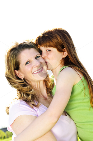 Mother and daughter hugging stock photo, Portrait of happy child hugging and kissing her mother by Elena Elisseeva
