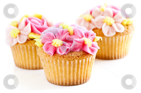 Cupcakes stock photo, Three tasty cupcakes with icing flowers on white background by Elena Elisseeva