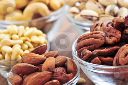 Bowls of assorted nuts stock photo, Many glass bowls of almonds walnuts pistachios and pine nuts by Elena Elisseeva