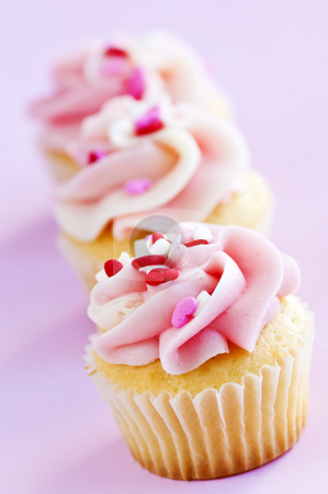 Cupcakes stock photo, Row of tasty cupcakes with icing and sprinkles by Elena Elisseeva