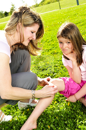 Mother putting bandage on child stock photo, Portrait of mother giving first aid to daughters cut knee by Elena Elisseeva