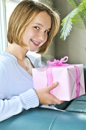 Teenage girl with present stock photo, Teenage girl with braces holding wrapped present and smiling by Elena Elisseeva