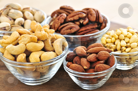 Bowls of nuts stock photo, Almonds, cashews pistachio and pine nuts in glass bowls by Elena Elisseeva