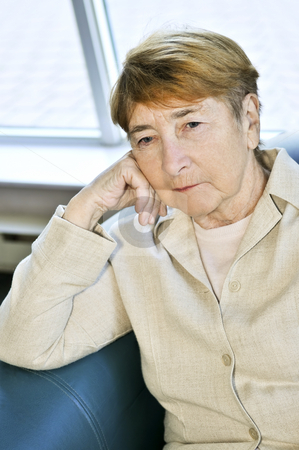 Sad elderly woman stock photo, Sad elderly woman sitting on a couch indoors by Elena Elisseeva