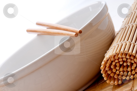 A tilted horizontal image of a pair of chopsticks on a white bow stock photo, A tilted horizontal image of a pair of chopsticks on a white bowl with a suhi rolling mat on a weaved placemat by Vince Clements