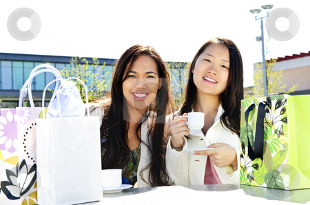 Girlfriends having coffee stock photo, Two girl friends sitting and having drinks at outdoor mall with shopping bags by Elena Elisseeva