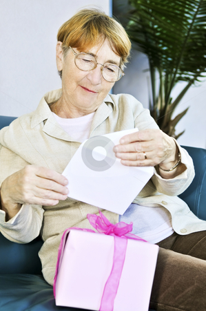 Old woman opening present stock photo, Elderly woman opening birthday card and present by Elena Elisseeva