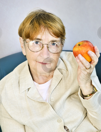 Elderly woman with apple stock photo, Elderly woman eating healthy holding a nutritious apple by Elena Elisseeva