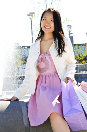 Asian woman shopping stock photo, Young korean woman with shopping bags at outdoor mall near fountain by Elena Elisseeva
