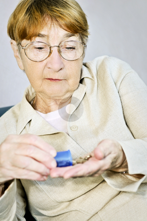 Elderly woman with medication stock photo, Senior woman pouring medication from pill bottle by Elena Elisseeva