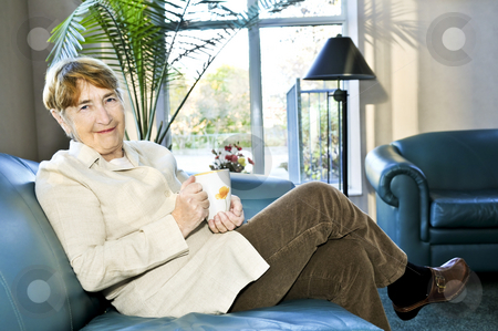 Elderly woman relaxing stock photo, Senior woman sitting and smiling happily with cup of tea by Elena Elisseeva