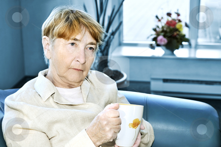 Sad elderly woman stock photo, Sad elderly woman sitting with cup of tea by Elena Elisseeva