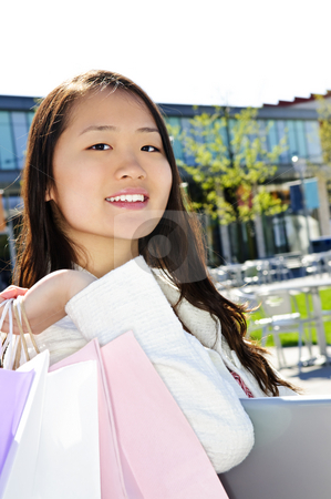 Asian woman shopping stock photo, Young korean woman with shopping bags at outdoor mall sitting on bench by Elena Elisseeva