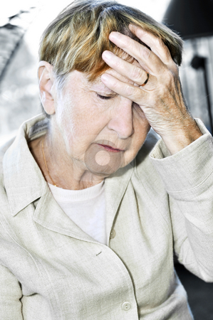 Elderly woman holding head stock photo, Sad senior woman holding her hand over forehead by Elena Elisseeva