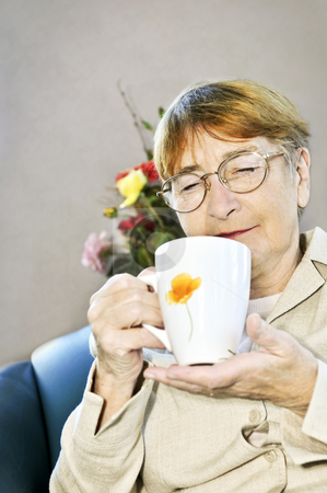 Elderly woman relaxing stock photo, Elderly woman sitting and relaxing with cup of tea by Elena Elisseeva