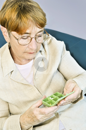 Elderly woman with pill box stock photo, Elderly woman holding pill box with medication by Elena Elisseeva