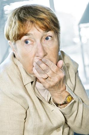 Scared elderly woman stock photo, Afraid elderly woman looking sideways in surprise by Elena Elisseeva