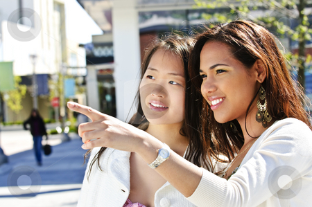 Young friends pointing stock photo, Two young girlfriends at outdoor mall pointing by Elena Elisseeva