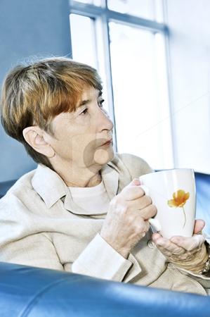 Sad elderly woman stock photo, Sad elderly woman sitting with cup of tea by Elena Elisseeva