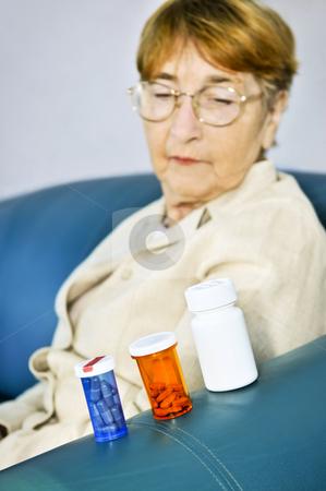 Elderly woman looking at pill bottles stock photo, Elderly woman looking at pill bottles with medication by Elena Elisseeva
