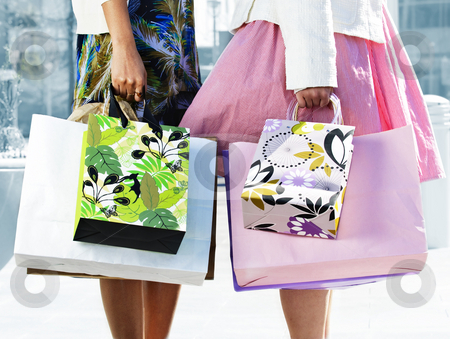 Women holding shopping bags stock photo, Two young girl friends holding shopping bags at mall by Elena Elisseeva