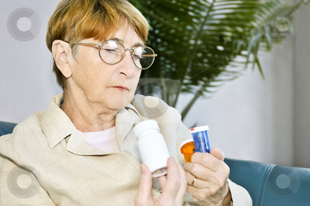 Elderly woman reading pill bottles stock photo, Elderly woman reading warning labels on pill bottles with medication by Elena Elisseeva