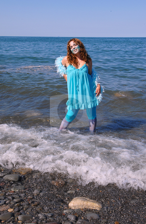The water girl. stock photo, The woman, representing water, dressed in blue, standing on the shore of lake Ontario in bright sunshine and the waves coming to shore. by Horst Petzold