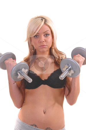 Young woman exercising. stock photo, A young pretty woman in gray shorts and black bra exercising with dumbbells for white background in the studio. by Horst Petzold