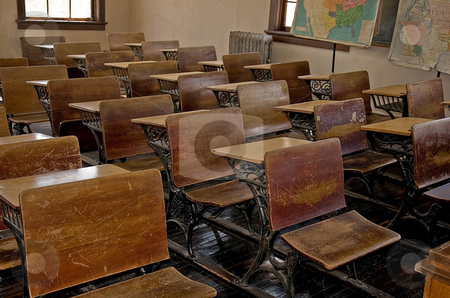 Antique Old School Classroom stock photo, This photo is an antique, turn of the century old school classroom with the wooden desks, wood floors, old radiator and vintage maps. by Valerie Garner