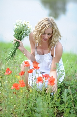Blonde woman picking flowers stock photo, Young blonde woman picking flowers by Alexander Dobrovodsky