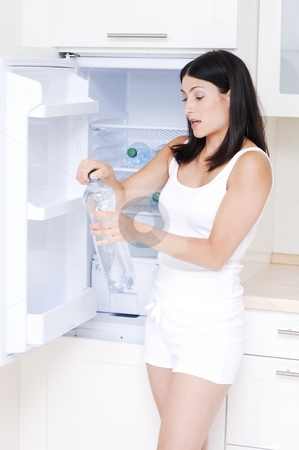 Woman in kitchen stock photo, Young dark haired woman in a kitchen opening a bottle of water by Alexander Dobrovodsky