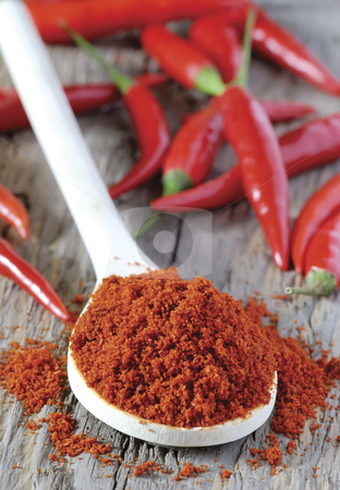 Chilli powder stock photo, Close up of spoon heaped with chilli powder with red chillies in background by Paul Turner