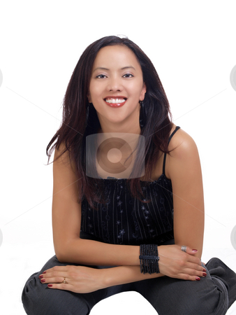 Young hispanic woman kneeling on floor in pants stock photo, Young latina woman in grey pants on floor by Jeff Cleveland