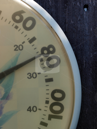 Closeup of dial thermometer outdoors against fence stock photo, Seventy-nine degrees on outdoor thermometer closeup by Jeff Cleveland