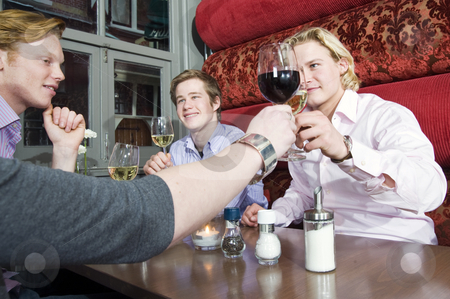 Toasting stock photo, A group of friends toasting their wine glasses in a restaurant. by Corepics VOF