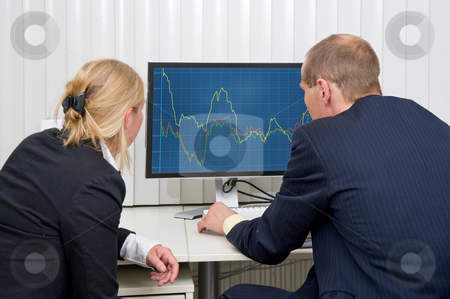Analyzing trends stock photo, Two brokers analyzing (sales) trends, displayed on a flat screen monitor by Corepics VOF