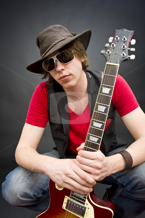 Young guitar player stock photo, A young, funky guitar player crouching with his instrument in his hands by Corepics VOF