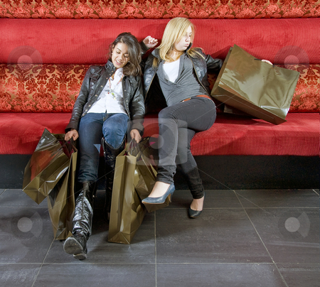 Two women resting after shopping stock photo, Two young women taking a rest in a trendy restaurant after shopping by Corepics VOF
