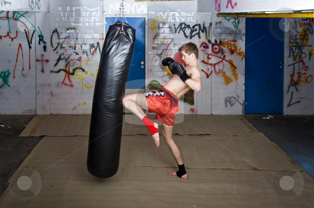 Knee kick stock photo, A muay thai figher giving a knee kick during a practice by Corepics VOF