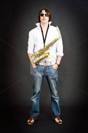 Cool saxophonist stock photo, Cool dude posing with a saxophone strapped around his neck by Corepics VOF